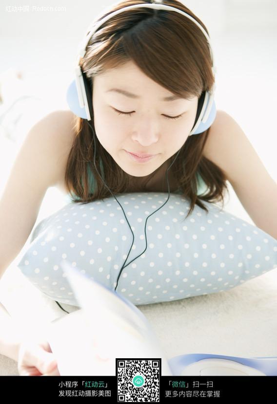 美女趴着抱这枕头听歌看书图片编号:240322