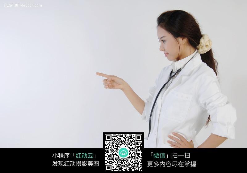 手指指着远方的美女医生设计图片