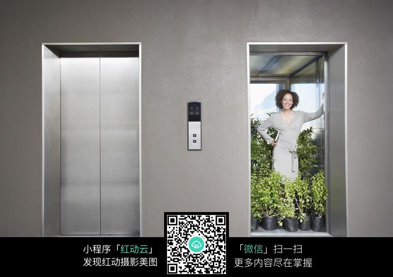 电梯中被绿色植物包围的美女图片 人物图片素