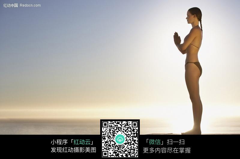 阳光下双手合十的泳衣美女设计图片