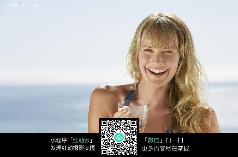 拿水杯大笑的外国美女设计图片