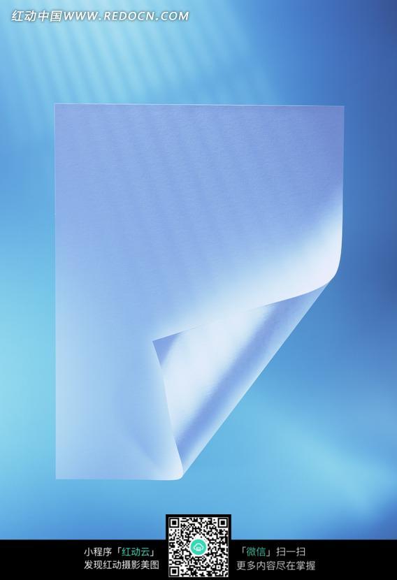 蓝色背景下卷起一角的纸张特写