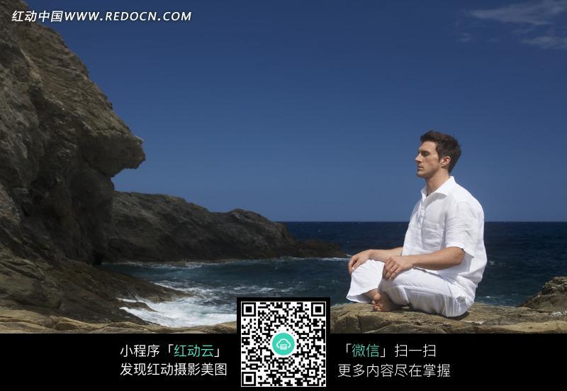 盘腿于海边打坐的男子图片