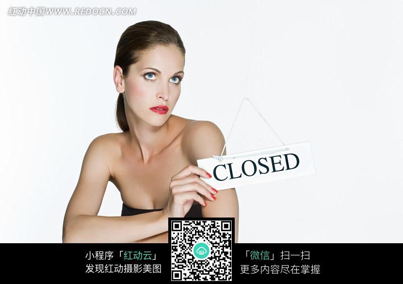 手拿广告牌的女模特照片
