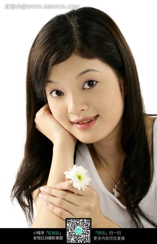 手拿一朵白色小花微笑的女模特图片 人物图片