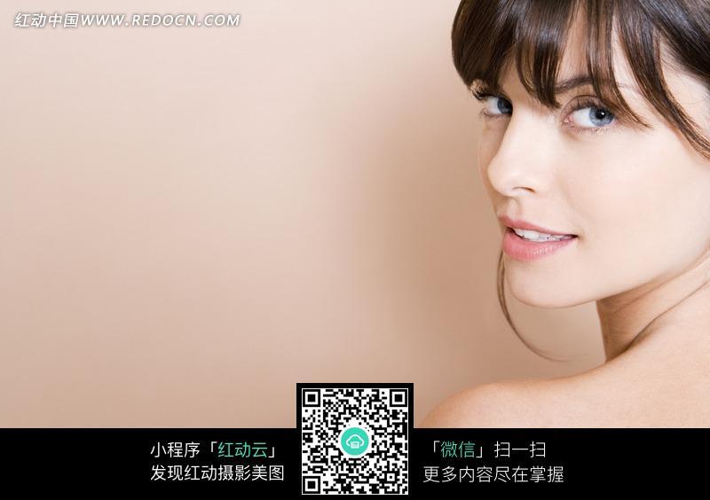 转头望的梳刘海的微笑的美女设计图片