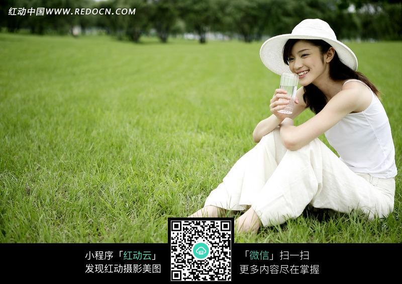 坐在草地上的白衣美女图片设计图片