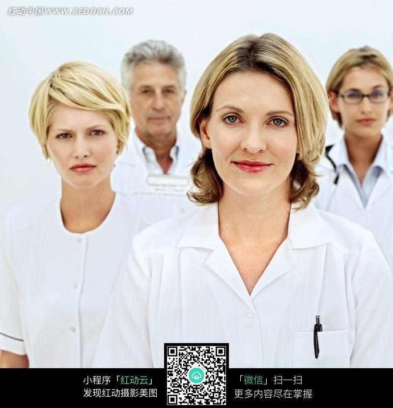 金发的微笑的女医生和背后的医生设计图片