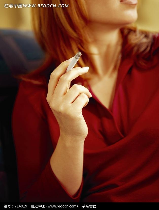 女人手里拿着点着的烟支