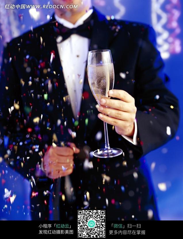 喜庆的彩色碎屑中举着玻璃酒杯的男子的手图片