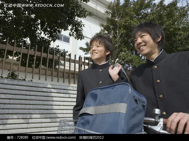 两分别背着和驮着书包微笑的日本男中学生图片