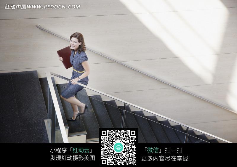 夹着文件夹上楼梯的女子设计图片