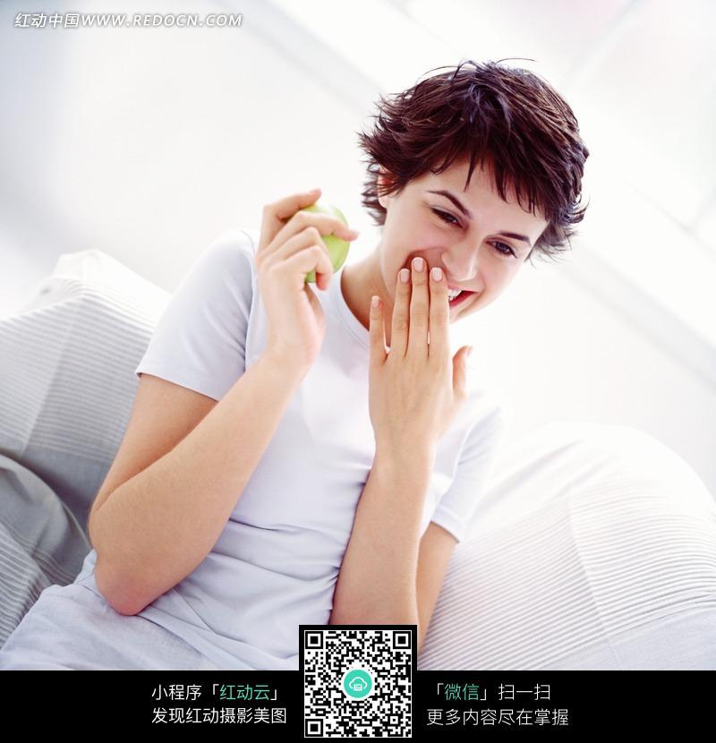 微笑拿着苹果掩嘴而笑的外国美女图片JPG图片