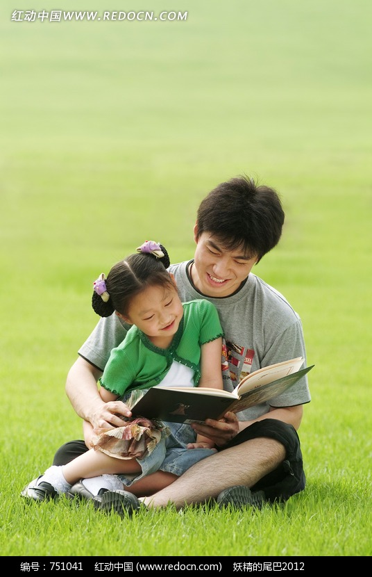 男人抱着小女孩看书坐在草地上看书
