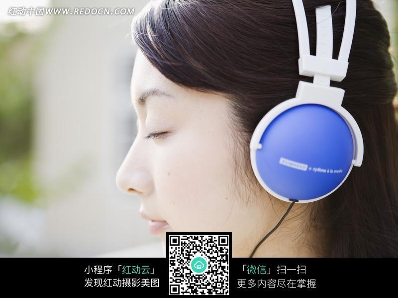 戴蓝色耳麦的女孩侧脸特写图片 人物图片素材