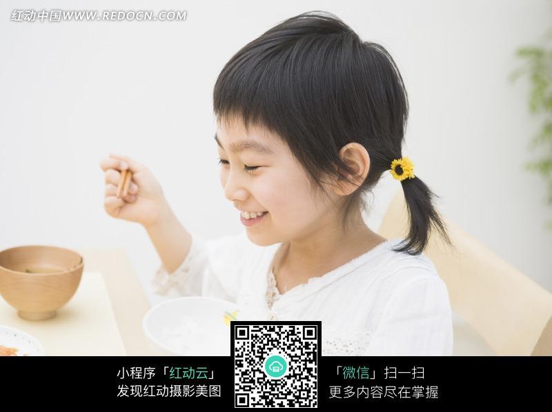 坐着拿着筷子吃饭的女孩设计图片