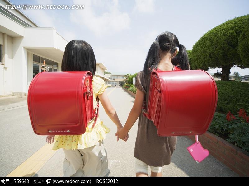 手牵手的背着红色书包的两个女孩的背影设计图片