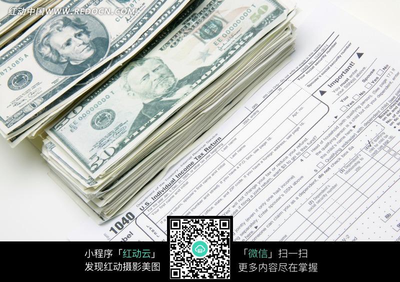 压在个人所得税申报表上的钞票图片