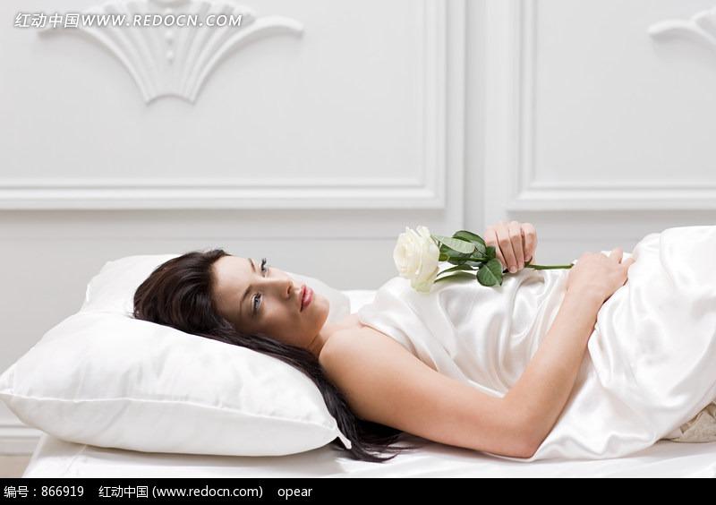 手拿白色玫瑰花躺在床上的外国美女图片