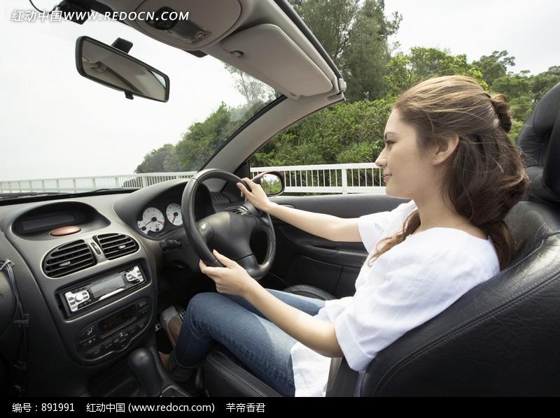 开篷车上在握住方向盘开车的白衣美女图片 人物图片