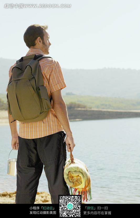 海滩沙地背着背包拿着铁桶和棉被的外国男士背影设计图片图片