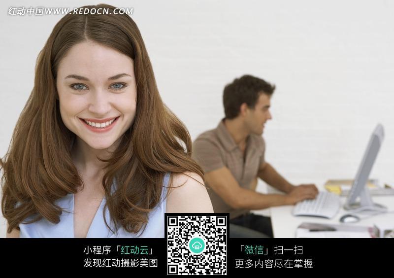 微笑的外国美女和玩电脑的男人设计图片