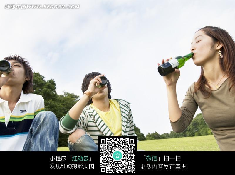 坐在草地上喝酒的三个男女设计图片