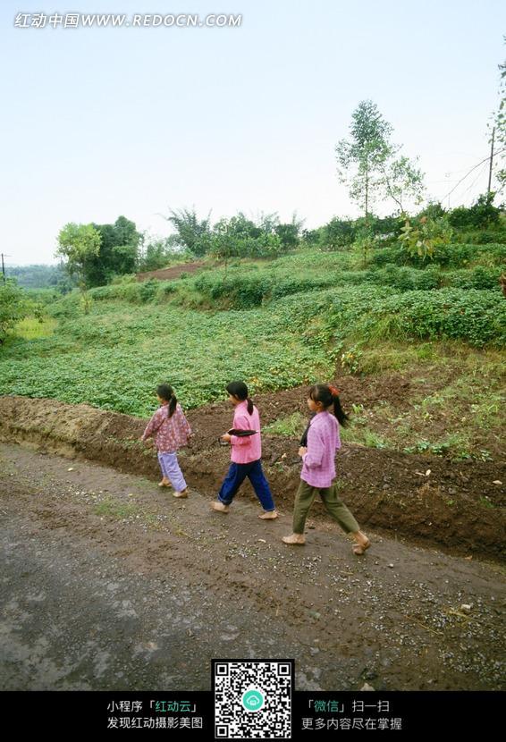 走在乡间小路上的三个农村女孩