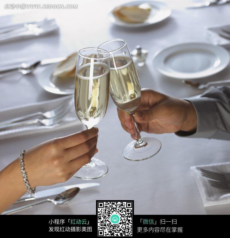 餐桌上举着酒杯相碰的一双手图片(编号:1018139)图片