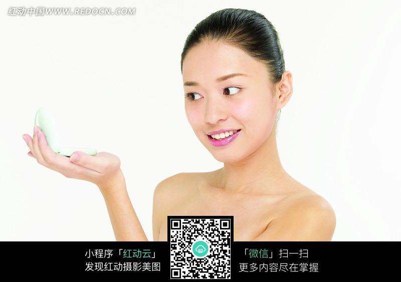 单手托着化妆镜照脸的美女图片编号:1019649