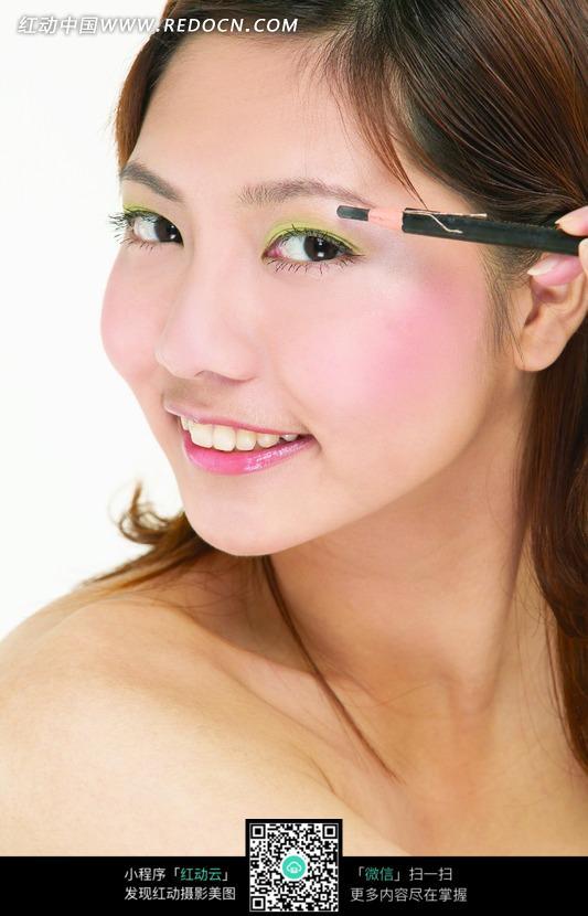 拿着炭笔画眉毛的美女图片 1020229