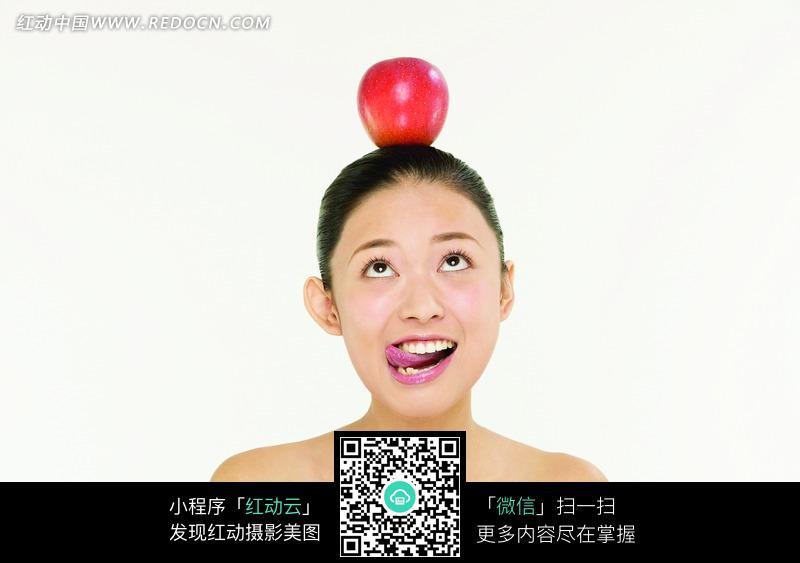 头顶苹果舔舌头的美女模特图片 人物图片素材