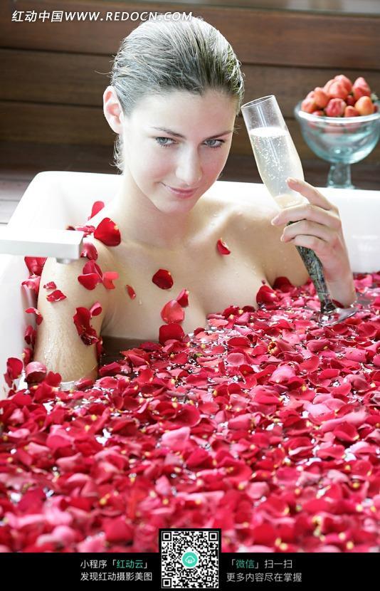 在漂浮着玫瑰花瓣的浴池里泡澡的外国美女设计图片