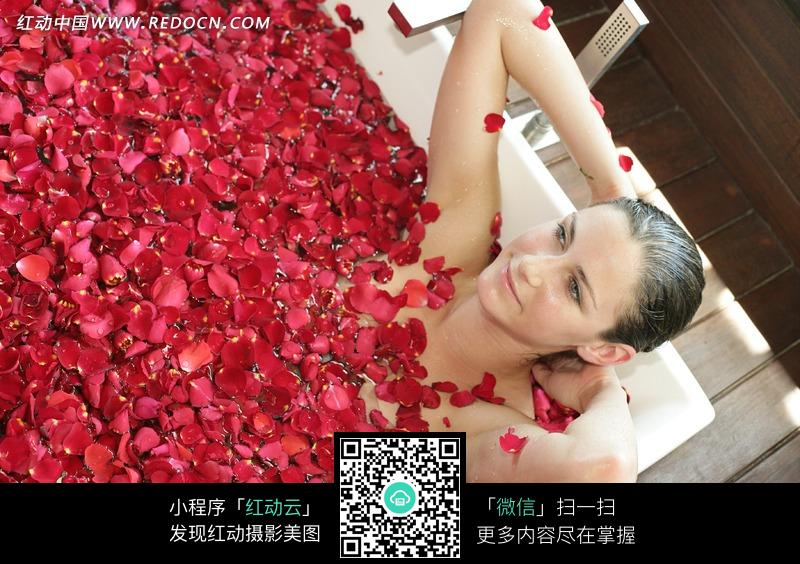 在漂浮着红色花瓣的浴池里泡澡的外国美女图片