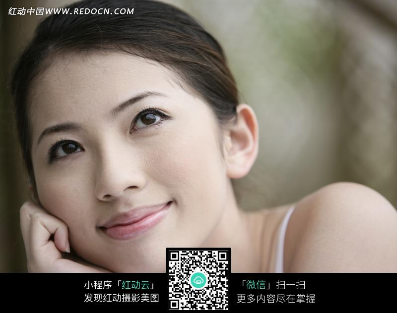 一只手撑下巴微笑的美女图片图片编号:1023603
