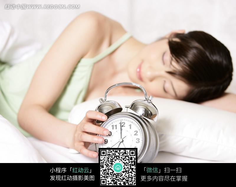 手拿闹钟躺在床上睡觉的美女图片编号:1023769