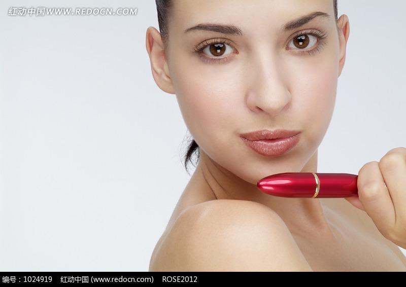 拿着红色唇膏的外国女人面部特写图片编号:1