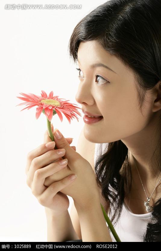 双手拿着粉色菊花放在脸前的女人图片编号:1025889