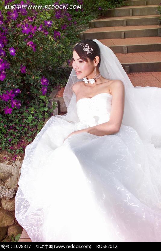 坐在台阶上穿白色婚纱的美女设计图片