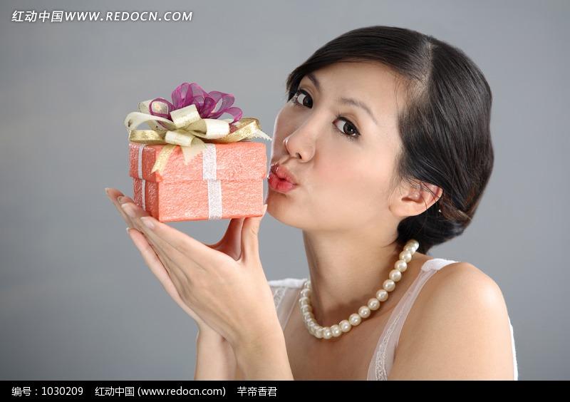 亲吻橙色礼品盒的美女设计图片