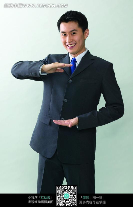 穿着西服的做高低手势的商务男士设计图片