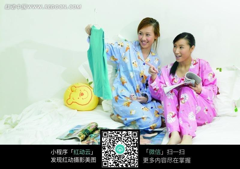看着挂衣架上的衣服的两个美女图片编号:1039295