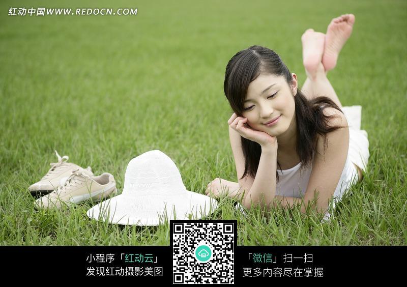 单手托腮趴在绿草地上的美女和一旁的帽子鞋子设计