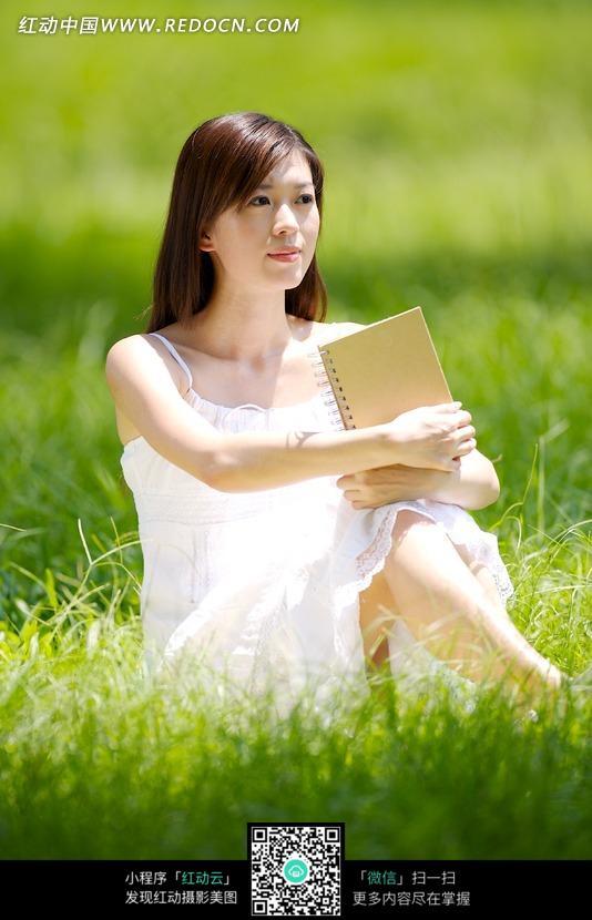 拿着书坐在草地上的美女图片编号:1047551