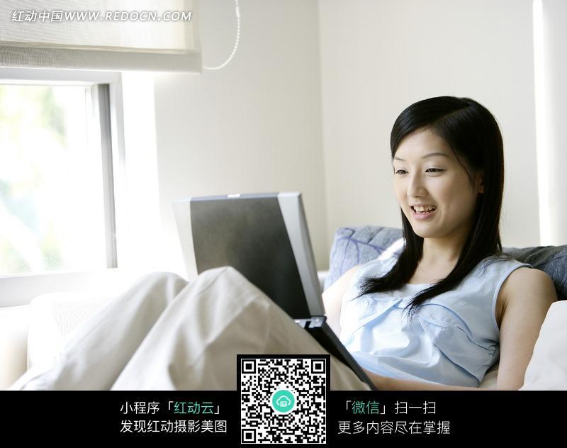 倚躺在沙发上微笑着玩电脑的美女图片编号:1049827