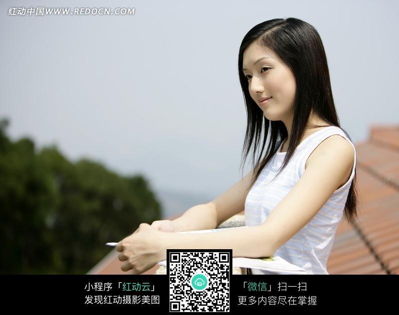 屋顶上靠在石栏杆微笑站立的美女图片编号:1049783