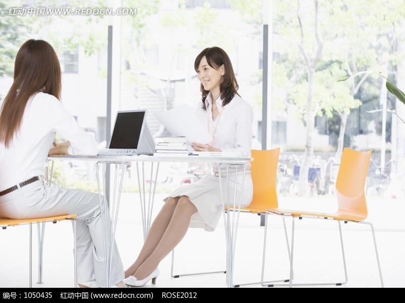 面对面坐在会议桌旁的两个职场美女图片