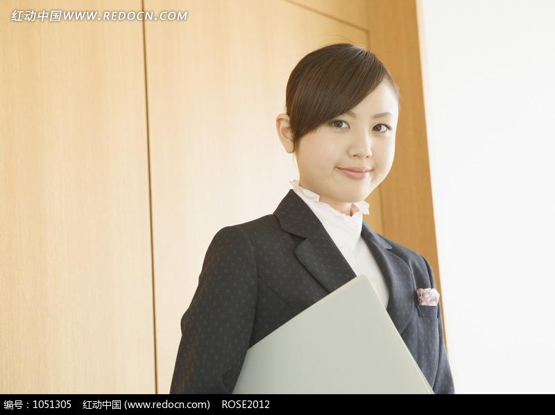 夹着文件夹穿黑色西装的女人图片(编号:1051305)
