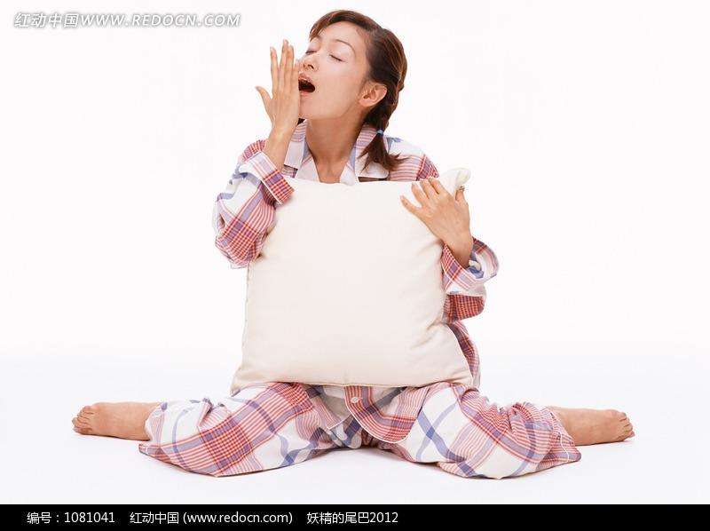 抱着靠枕打哈欠的美女设计图片