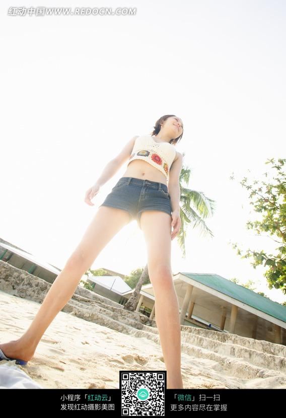 阳光下沙滩上叉腿站立的性感美女